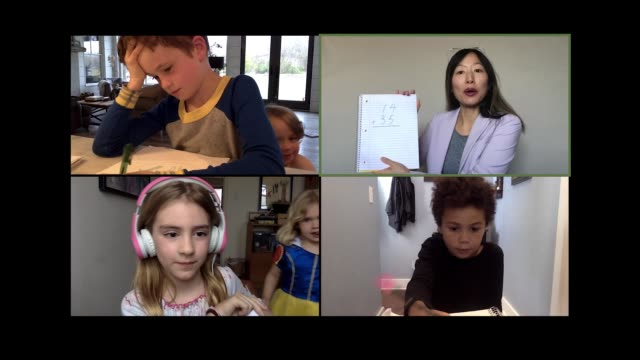 vídeos de stock, filmes e b-roll de elementary teacher virtually explains a math probelm to her young students via video call. - aprendizagem online