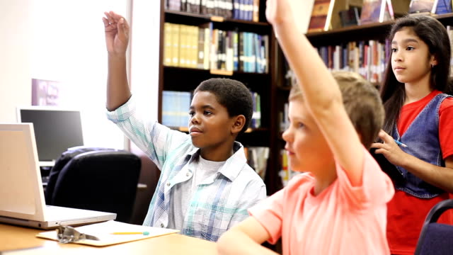 Elementary-age school children working together and answer questions by raising hands