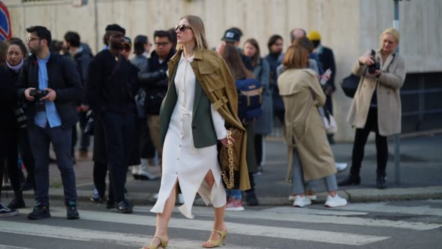 elena ricciardi wears sunglasses, a brown leather long coat, a white dress, a green khaki jacket, a brown bag with a golden chain strap, outside... - white dress stock videos & royalty-free footage