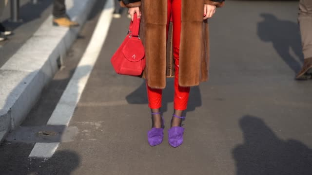 Eleonora Carisi wears a red beret hat a brown coat a red outfit purple shoes during Milan Menswear Fashion week Fall/Winter 2018/19 on January 14...