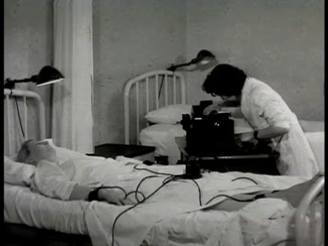 eletrocardiograph procedure request slip female patient reclined in bed female technician or nurse setting machine checking dial cu wrist connectors... - 1948 stock-videos und b-roll-filmmaterial