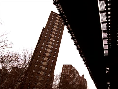 vidéos et rushes de elevated 125 street station subway train tracks, shadow of subway train moving down tracks. train moving overhead, brick highrise apartments near... - train aérien