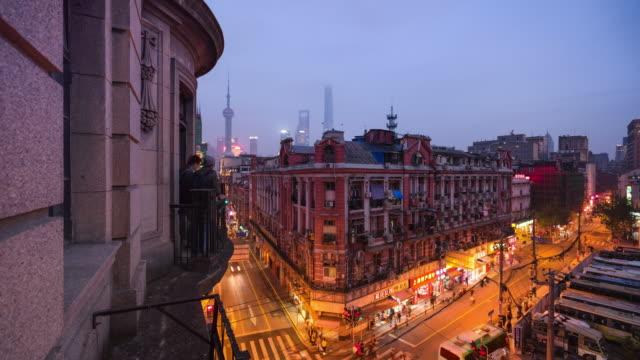 elevated balcony view of shanghai old street dusk to night transition - 東方明珠塔点の映像素材/bロール
