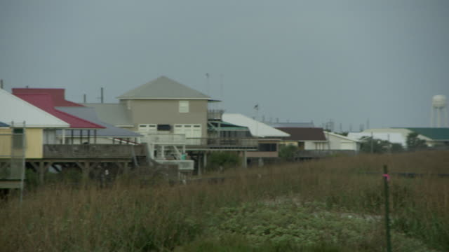 elevated homes face a beach in grand isle, louisiana. - stilts stock videos and b-roll footage