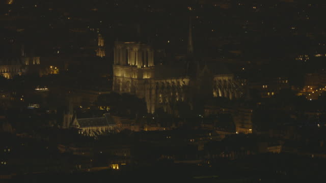 stockvideo's en b-roll-footage met elevated nighttime sequence of an illuminated notre dame de paris cathedral and surrounding rooftops on the île de la cité (4th arrondissement), paris, france. - charmant