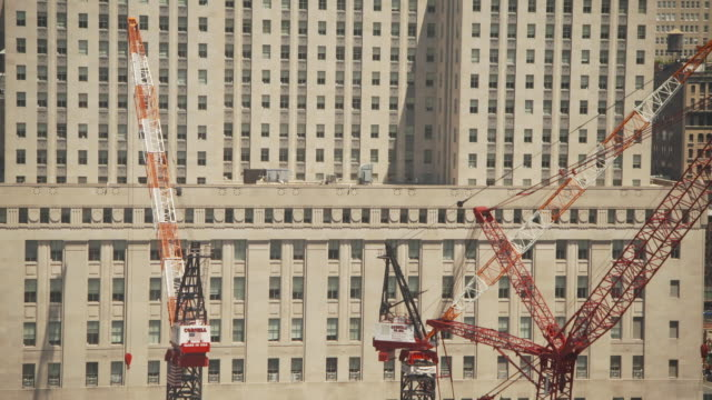 elevated sequence showing red and white cranes working on the new world trade center site in front of the federal office building 90 church street... - medium group of objects stock videos & royalty-free footage