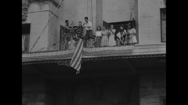 mws elevated shot of general douglas macarthur in middle of crowd of liberated prisoners while exiting building / ms elevated shot of macarthur... - awning stock videos and b-roll footage