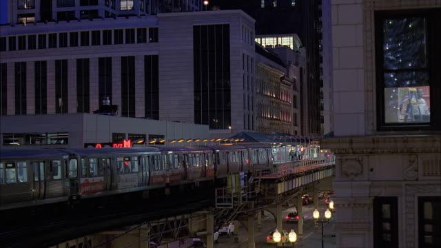 vidéos et rushes de ws elevated train and traffic on street at dusk / chicago, illinois, usa - métro de chicago