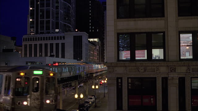 ws elevated train and traffic on street at dusk / chicago, illinois, usa - chicago elevated stock-videos und b-roll-filmmaterial