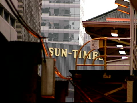 elevated train arriving at station with chicago sun-times building sign in background / chicago, illinois - hochbahn passagierzug stock-videos und b-roll-filmmaterial