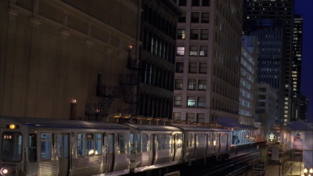 ws pan elevated train at dusk / chicago, illinois, usa - chicago elevated stock-videos und b-roll-filmmaterial