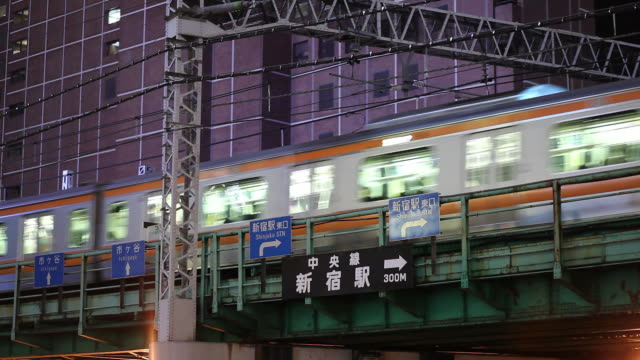 ws elevated train crossing industrial area at dusk / tokyo, japan - elevated train stock videos and b-roll footage