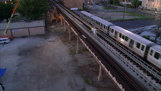 ws ha elevated train crossing industrial area at sunset / chicago, illinois, usa - chicago elevated stock-videos und b-roll-filmmaterial