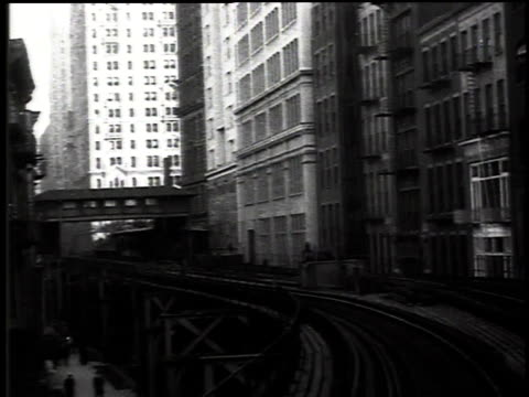 1916 montage elevated train going down a track and passing buildings / new york, new york, united states - 1916年点の映像素材/bロール