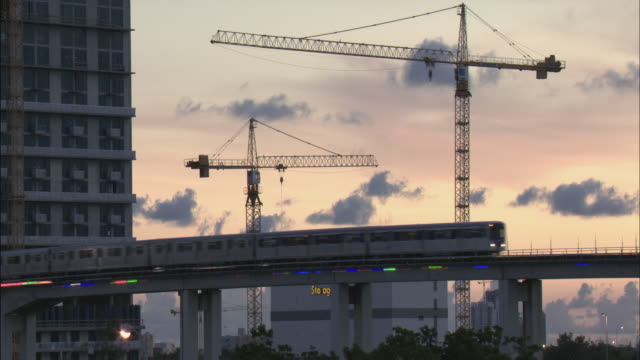 ws elevated train moving past construction cranes at sunset/ miami, florida - hochbahn passagierzug stock-videos und b-roll-filmmaterial