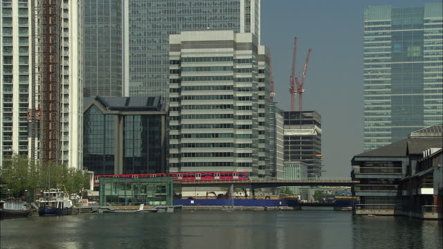 ws elevated train passing docklands waterfront/ london, england - london docklands stock videos & royalty-free footage