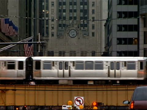 elevated train passing on tracks with chicago board of trade building in background / american flags hanging on poles in foreground / chicago, illinois - hochbahn passagierzug stock-videos und b-roll-filmmaterial