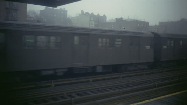 1966 MONTAGE Elevated train passing through station at dusk / Manhattan, New York