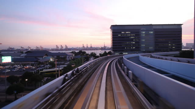 WS POV Elevated train pulling into station at dusk / Tokyo, Japan
