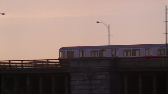 MS Elevated train traveling over a bridge past skyscrapers / Massachusetts, United States