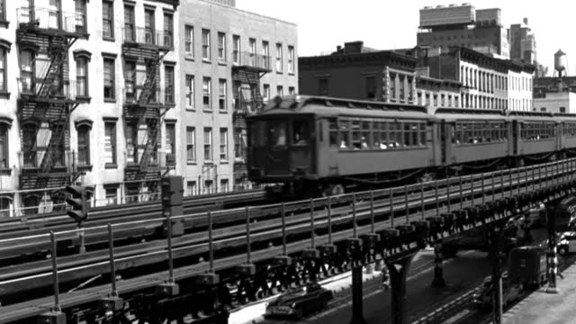 elevated trains drive on tracks over street traffic below. - elevated train stock-videos und b-roll-filmmaterial