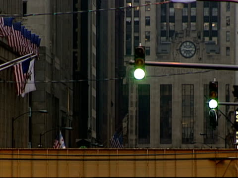 vídeos de stock e filmes b-roll de elevated trains passing on tracks with chicago board of trade building in background / traffic light changing colors as traffic moves in foreground / american flags hanging on poles from buildings / chicago, illinois - metro de chicago