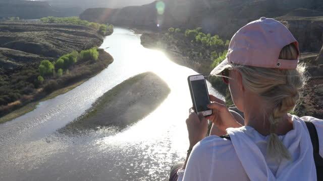 stockvideo's en b-roll-footage met opgeheven mening van vrouwelijke wandelaar op canionrand boven rivier, zonsopgang - hoofddeksel