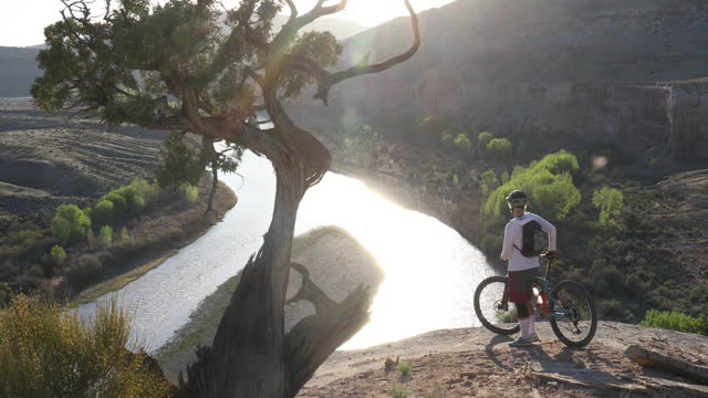 elevated view of female mountain biker on canyon rim above river, sunrise - cliff stock videos & royalty-free footage