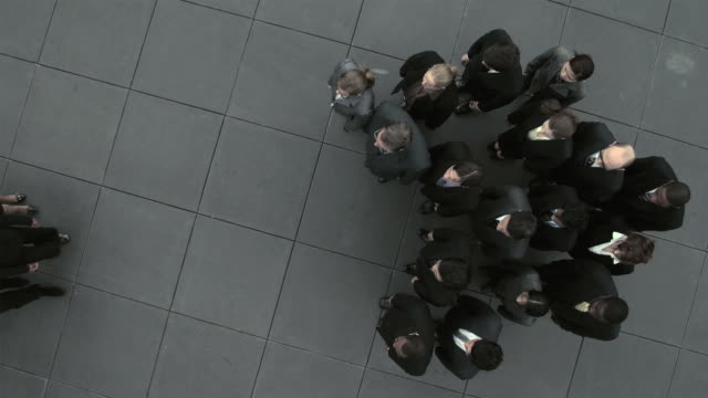 Elevated view of group of businesswomen walking to join other businesspeople