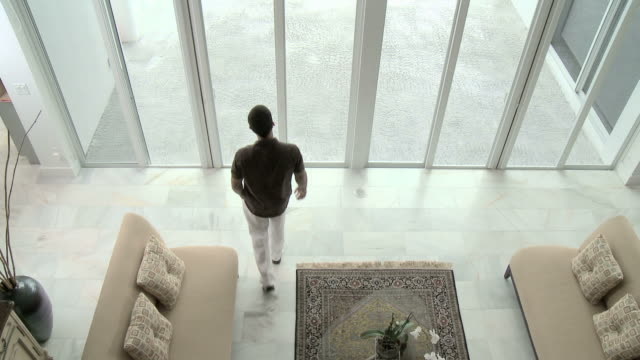 Elevated view of man entering living room, looking out of window, walking and using cellphone