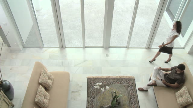 Elevated view of man on sofa and woman walking through room