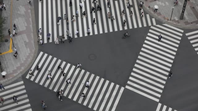 Elevated view of pedestrians crossing a road in the Yurakucho area of Tokyo Japan on Monday June 5 2017