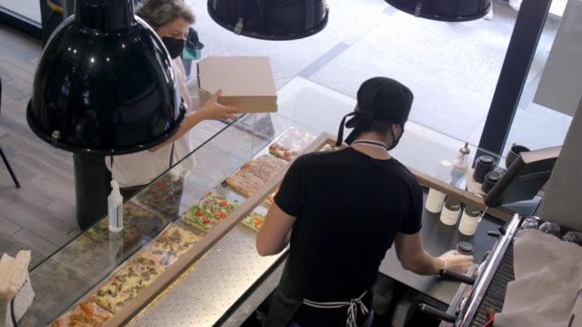 フェイスマスクを着用してピザとコーヒーを取り出すピックアップの高い眺め - 外食産業関係の職業点の映像素材/bロール