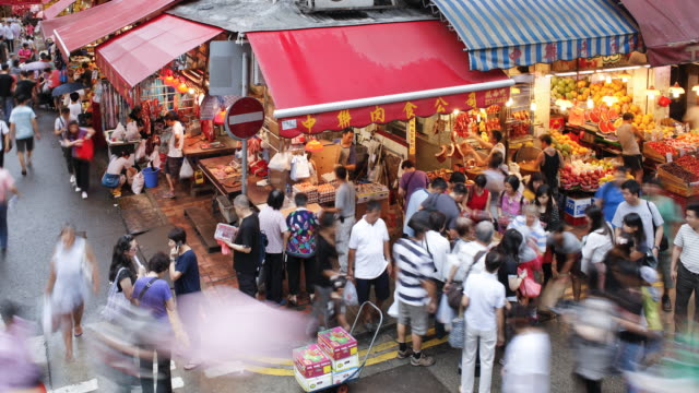 elevated view of shoppers and the traditional chinese stalls in wanchai market, hong kong island, hong kong, china - time-lapse - wanchai stock videos and b-roll footage