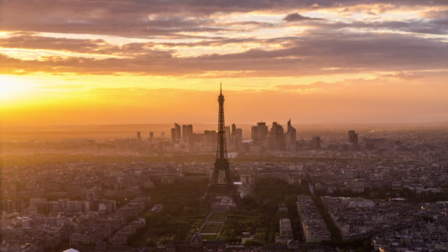 Elevated view of the Eiffel Tower, city skyline and La Defence skyscrapper district in the distance, Paris, France, Europe - Time lapse