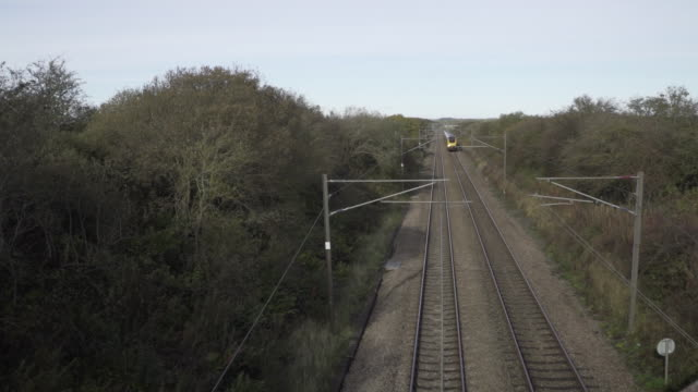 elevated view of train passing under rail bridge uk - woodland stock videos & royalty-free footage