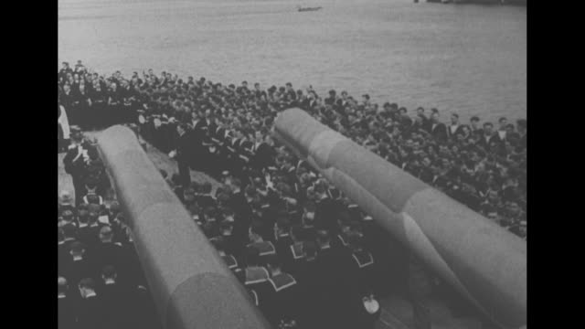 PAN elevated views of British sailors gathered on deck of battleship HMS Prince of Wales ship's guns in foreground / MS US President Franklin D...