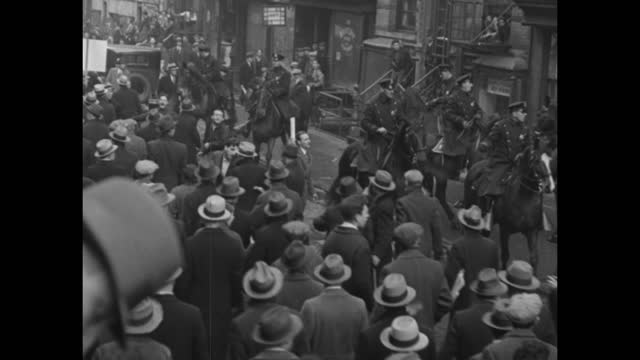 elevated views of crowd gathered as communists demonstrate with picket signs, other kids and adults wandering around amid the excitement / elevated... - 1930 video stock e b–roll