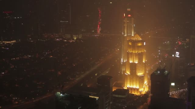 elevated views of illuminated street traffic moving along a road as buildings stand shrouded in haze at night in kuala lumpur malaysia on monday oct... - petronas twin towers stock-videos und b-roll-filmmaterial