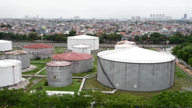 elevated wide pan l r of fuel storage tanks at a pt pertamina facility at tanjung priok port in jakarta indonesia wednesday jan 21 various elevated... - 軍用輸送車点の映像素材/bロール