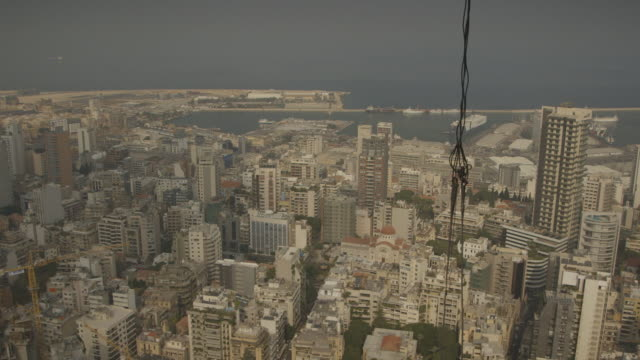 vidéos et rushes de elevated wide shot from a construction site showing the mar nkoula/nicola (st. nicholas) greek orthodox church and the port of beirut in the achrafieh area, lebanon. - mar