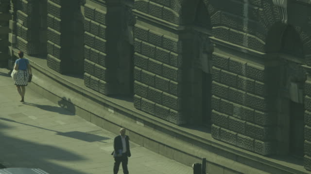 elevated wide shot of people walking on a pavement alongside the grand walls of the old bailey criminal court on newgate street in the city of london, uk. - オールドベイリー点の映像素材/bロール