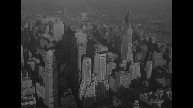 Elevation beauty shot Manhattan cityscape with Chrysler Building at right center and Waldorf Astoria Hotel at left rear / LS traffic in Manhattan...