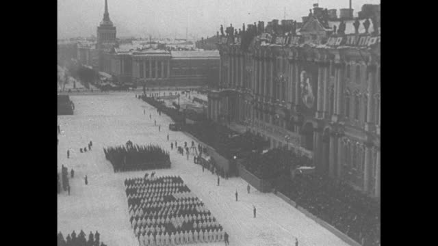 elevation shot russian military parade with flags, athletes march behind them in palace square in leningrad , building in bkgd, snow on ground /... - soviet military stock videos & royalty-free footage