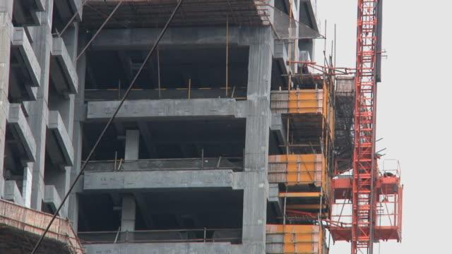 stockvideo's en b-roll-footage met ms la elevator moving up side of building under construction / ningbo, zhejiang, china - ningbo