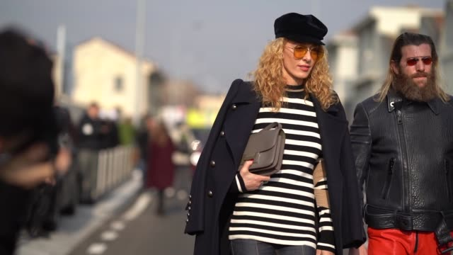 Elina Halimi wears a beret hat a striped top a jacket during Milan Menswear Fashion week Fall/Winter 2018/19 on January 14 2018 in Milan Italy
