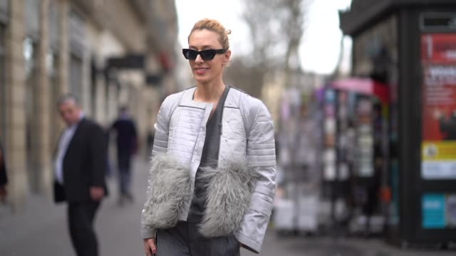 stockvideo's en b-roll-footage met elina halimi wears sunglasses a gray jacket with fur gray pants red shoes a hermes bag outside elie saab during paris fashion week haute couture... - jas