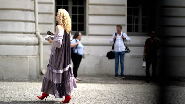 Elina Halimi wears sunglasses a ruffled purple dress red shoes a red choker outside the Zuhair Murad during Paris Fashion Week Haute Couture...