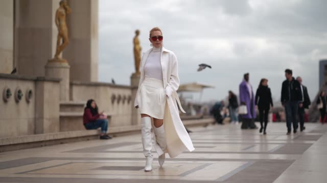 stockvideo's en b-roll-footage met elina halimi wears sunglasses a white coat a white turtleneck top a skirt white leather thigh high boots outside ann demeulemeester during paris... - coltrui
