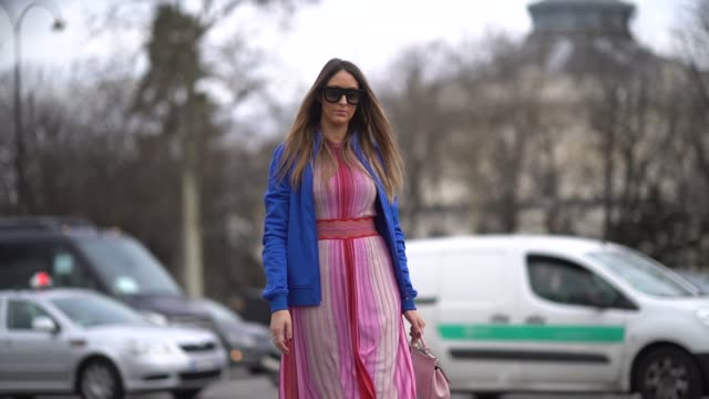 Elisa Taviti wears a blue jacket a pink and red dress red boots outside Chanel during Paris Fashion Week Womenswear Fall/Winter 2018/2019 on March 6...